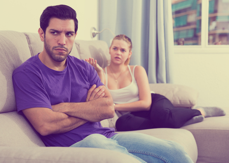Upset young man sitting on sofa at home with disgruntled woman behind