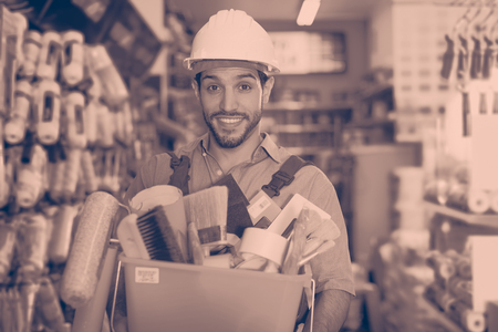 Satisfied young foreman standing near racks in paint store holding basket with tools