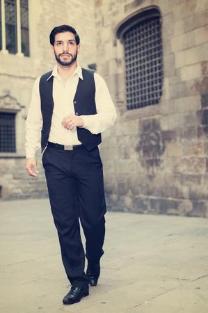 Portrait of handsome man in formalwear walking along ancient street