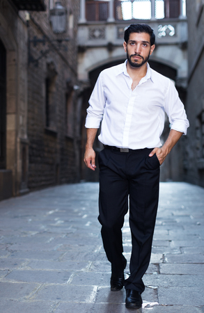 Portrait of handsome man in formalwear walking along ancient street  Stock Photo