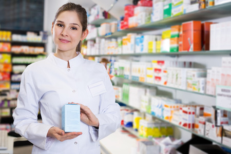 Portrait of young woman pharmacist who is standing with medicine on her work place in apothecary. Stock Photo