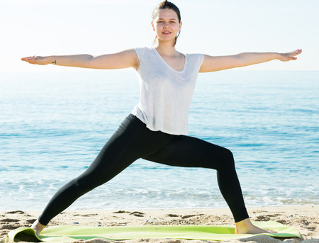 Adult woman in white T-shirt is stretching on the beach. Imagens