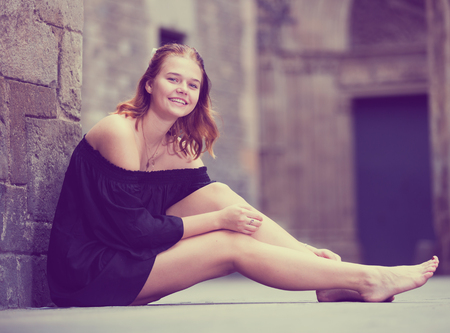 Cheerful girl sitting barefoot near the brick wall in dress outdoors Foto de archivo
