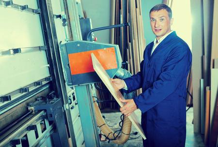 man wearing protective workwear cutting plywood using electric saw machinery