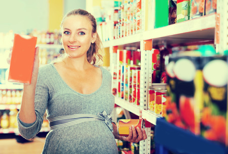 Young pregnant is demonstrating her choice in grocery department.