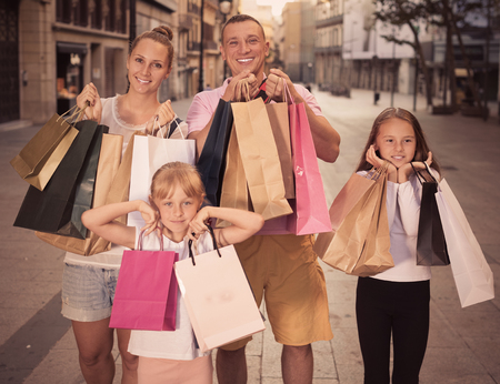 Happy man and woman  with children standing and holding shopping bags in city Stock Photo