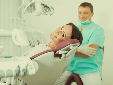 smiling woman patient with dentist professional sitting in medical room Stock Photo