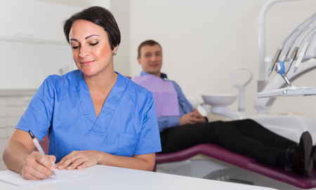 adult dentist in medical center with patient in chair indoors Stock Photo