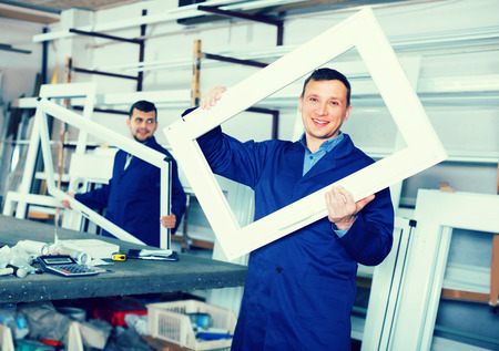 Two workmen are inspecting PVC manufacturing output in workshop.