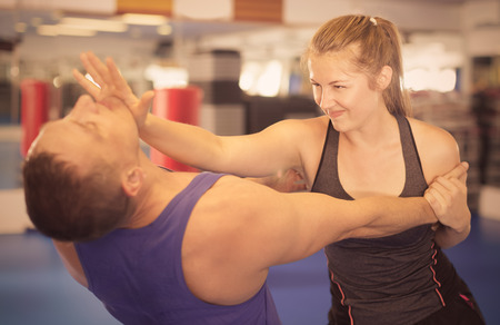 Young woman is fighting with trainer on the self-defense course for woman in sport club Archivio Fotografico