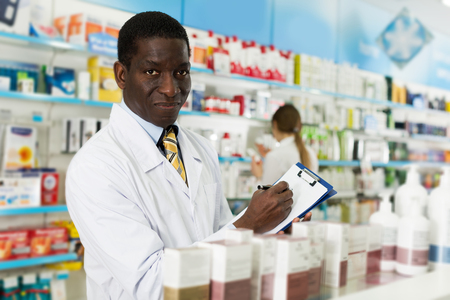 smiling confident African American pharmacist taking inventory of medicines in pharmacy Stock Photo
