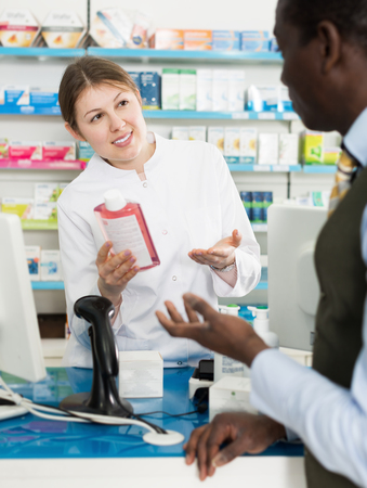Professional female pharmacist giving medicines to adult man customer in drugstore