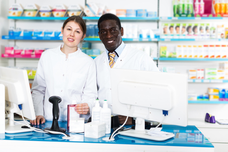 Two professional pharmacists working behind counter in modern pharmacy