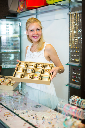 portrait of cheerful female jeweler with bracelet collection in shop with bijouterie