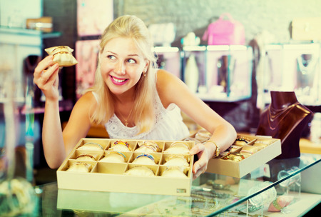 Young woman seller displaying bracelets in accessorizes and bijouterie store Stock Photo