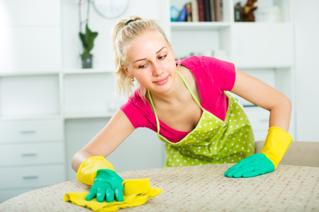 young blond girl in protective apron and gloves cleaning surfaces at home