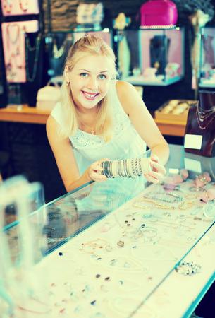 Happy young woman buying bracelet in bijouterie store