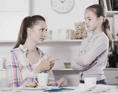 Young mother scolding her daughter for bad behavior and mistakes Stock Photo
