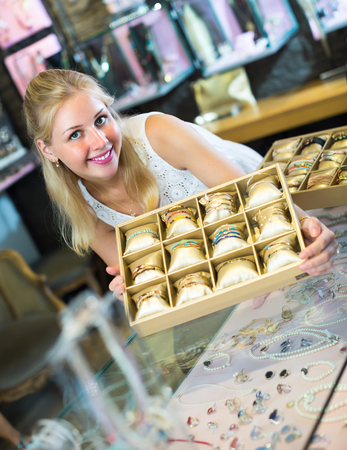 friendly smiling young female jeweler showing bracelet collection in bijouterie boutique  Stock Photo