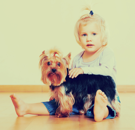 Little female child holding Yorkshire Terrier and smiling