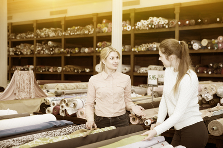 Polite female seller helping young woman in choice of interesting cloth in textile shop Stock Photo