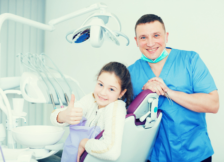 Smiling male dentist standing near satisfied teen girl showing thumbs up after dental treatment  写真素材