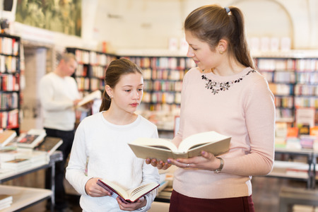 Attractive young woman with daughter looking for interesting books at library