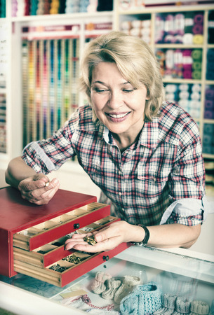 Portrait of mature cheerful female customer standing next to box with metallic fasteners in assortment at a shop Stock Photo