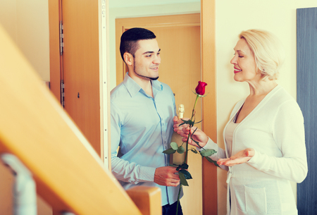 handsome man and elderly woman standing at doorway