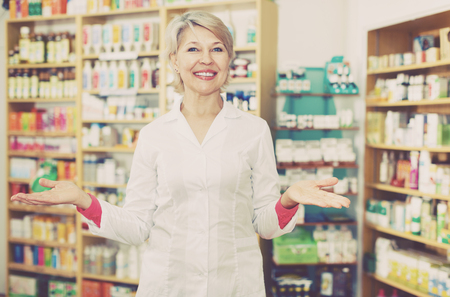 Smiling female worker checking assortment of cosmetics in shop