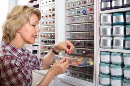 blonde mature housewife choosing various buttons in sewing store  Stock Photo