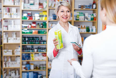 Cheerful seller recommending care products to customer in specialized shop