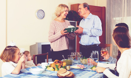 Happy family member receiving present from relatives at table Banque d'images