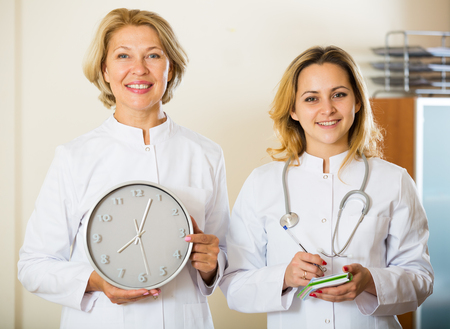 Time for appointment: mature and young doctors with clock