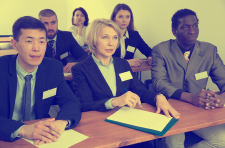 Portrait of focused people of different nationalities during business seminar in lecture hall