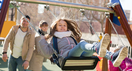 Smiling family of four spending time together at children swings