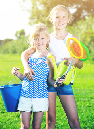 Two smiling little sisters posing with toys on green meadow