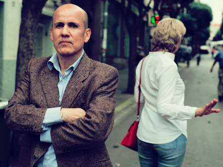 irritated senior man standing back to annoyed woman outdoors