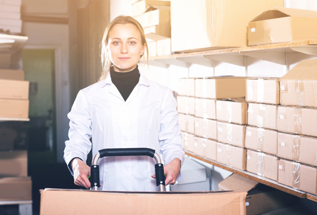 Portrait of young female worker transporting cart cardboard  cases in storage Stok Fotoğraf