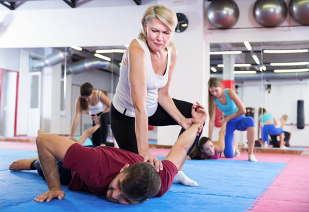 Mature female is training self-defence moves in pair with coach in fitness gym Archivio Fotografico