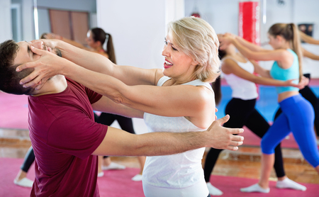 Sporty glad positive mature woman with her instructor are training self-defence moves in gym.