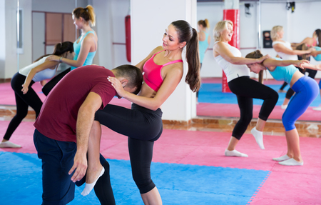 Sporty vigorous female with her trainer are doing self-defence moves in gym Archivio Fotografico