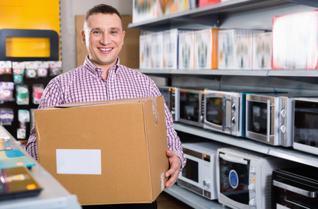 Glad cheerful positive man with packed purchases in  household appliances section in shop Foto de archivo