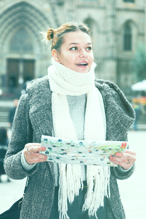 young female in the historical city center in scarf with map