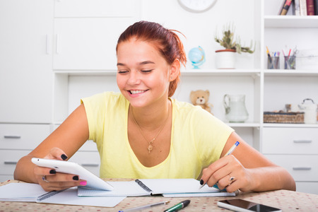 cheerful young female teenager studying with notes indoors