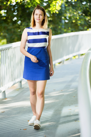 Smiling female in fashion dress walking along in park on city bridge surrounded by trees Stock Photo
