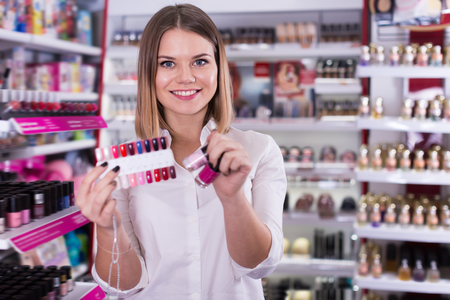 Cheerful female seller offering stylish colors of nail varnish on palette in cosmetic shop