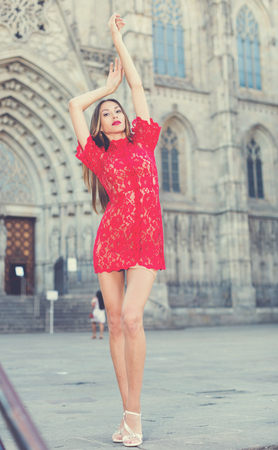 portrait of sexy young cheeful french woman in red dress walking in the old city