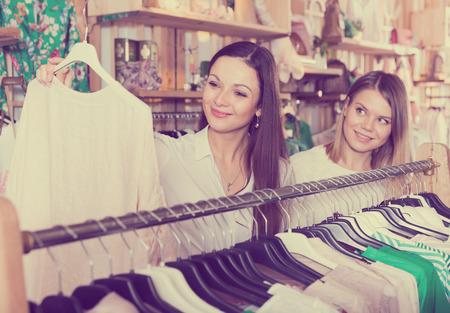Portrait of smiling female friends choosing sweater in the modern shop