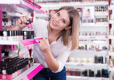 Positive girl shopping in cosmetics shop, choosing new nail polishes